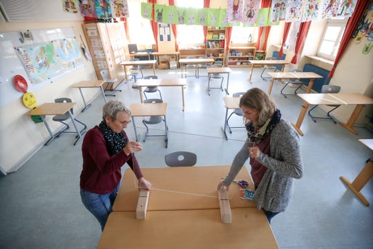 Staff install a plexiglass pane on the teacher's table during preparations for reopening the temporarily-closed Schloss-Schule elementary school on April 21, 2020 in Heppenheim, Germany.