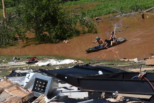 Brianna Snoddy (right) and her brother, Aden Snoddy, paddle on Bayou Boeuf as they try to salvage items scattered by Wednesday night's tornado. Their dog, Mozzie, jumped into the water as they searched.