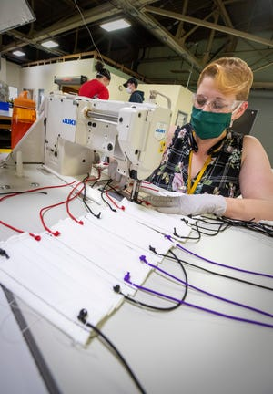 Wendy Wreyford, an office administrator at the Puget Sound Naval Shipyard, helps makes masks in the shipyard's sail loft.