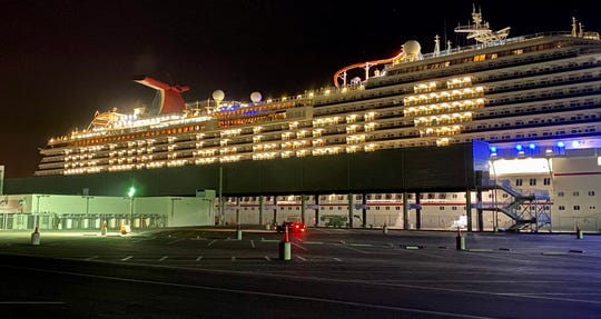 "The idled Carnival Breeze delivers a ""We Will Be Back"" message written in cabin lights."