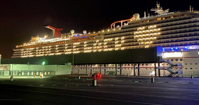 """The idled Carnival Breeze delivers a """"We Will Be Back"""" message written in cabin lights."""