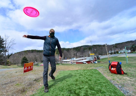 Andy Patari practices his throw before playing a game of frisbee golf as signs around Living Memorial Park in Brattleboro, Vt., reminds people to stay six feet apart because of COVID-19, Thursday, April 16, 2020.