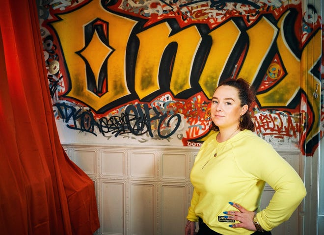 Alisha Dykema, a tattoo artist and owner of Onyx Ink on Burlington's Church Street, poses in June 2019 with graffiti by Jelani O'Connor. Dykema closed her studio on March 17, 2020 to comply with a statewide shut-down order due to the new coronavirus.