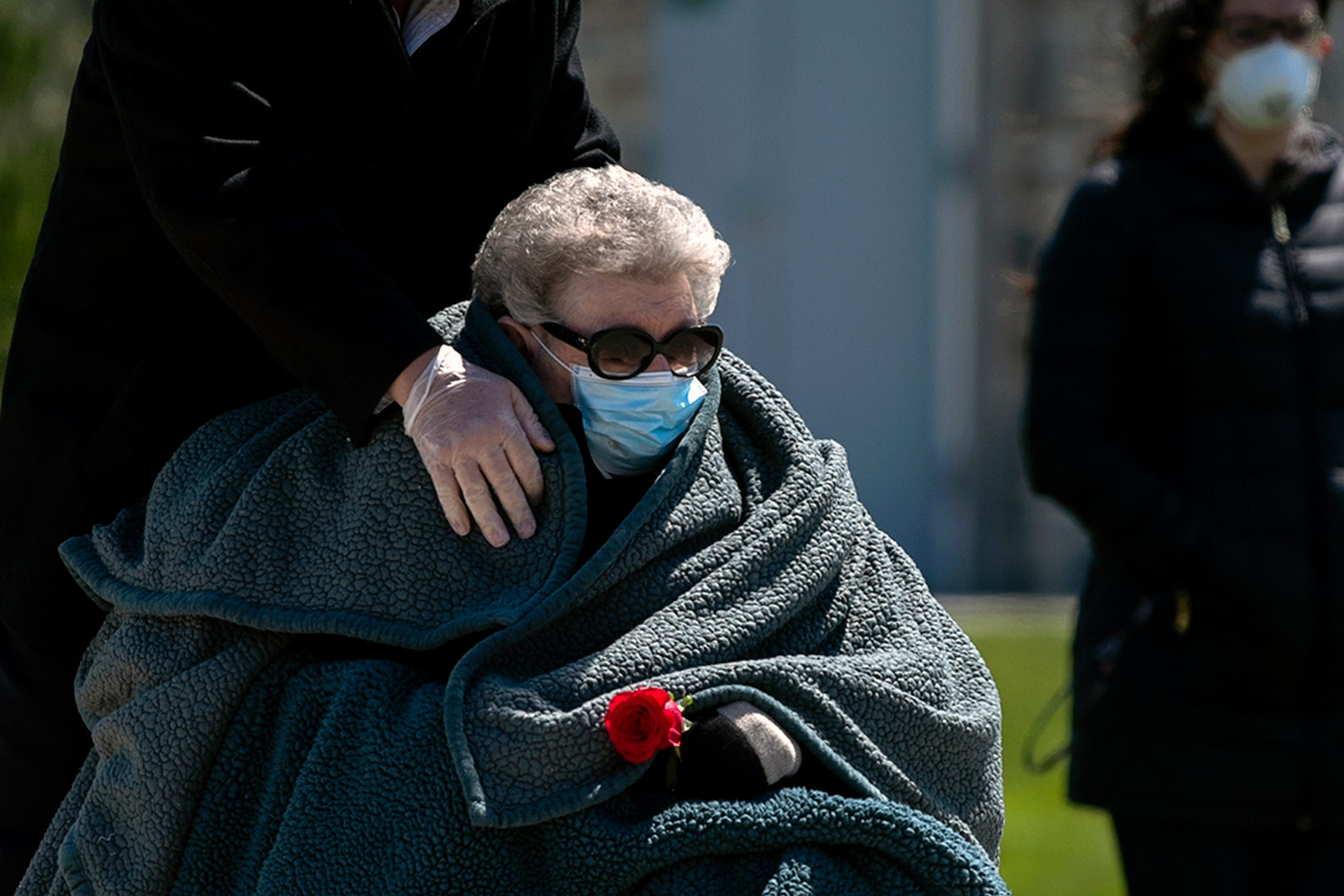 "Elizabeth ""Betty"" Taggart, 92, is embraced by her son Kirk Taggart as she mourns her husband Herman Taggart Wednesday, April 22, 2020 at Gloucester County Veterans Cemetery in Williamstown, N.J. Elizabeth and Herman were high school sweethearts and got married in 1949 following his World War II service in the Navy. ""We plan on having a second memorial when all this settles. In our family, closure for us has always been congregation, being together and laughing. We don't have that now. We have to go back to our homes and isolate. That for me has been the toughest challenge,"" said Herman's daughter Lynn Taggart."