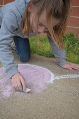 Reese Vance-Adams, 6, works on her chalk art for the sidewalk chalk contest. The activity is the second to be hosted by the First Capital Pandemic-Safe Activities group.