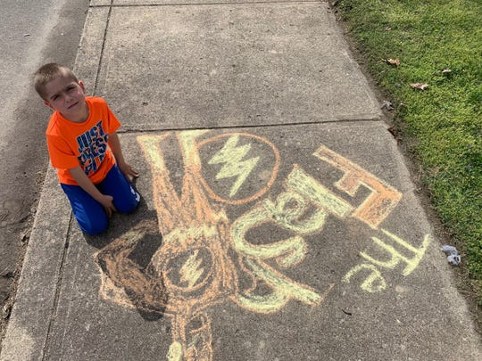 Brodie Vance-Adams, 7, creates superhero-themed sidewalk chalk art for a contest hosted by the First Capital Pandemic-Safe Activities group. Each week the group organizes a new activity for community members to participate in while practicing social distancing.