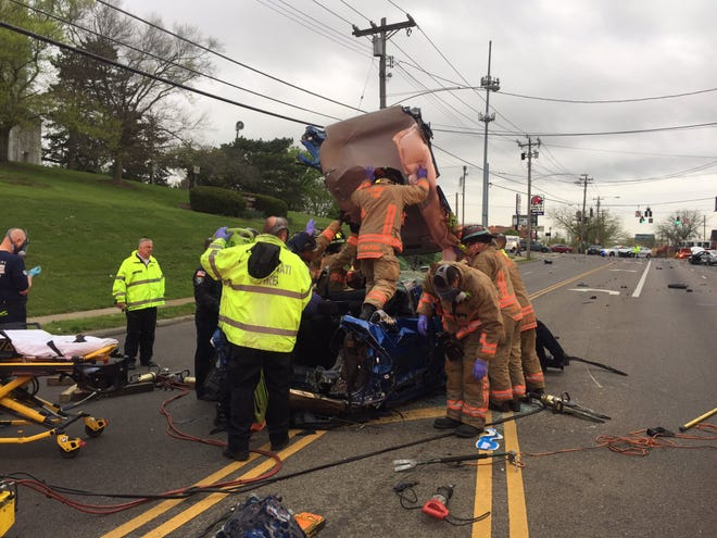Firefighters push the roof off a car involved in a crash Thursday morning near the 5400-block of Colerain Avenue to pull a patient out of the car.