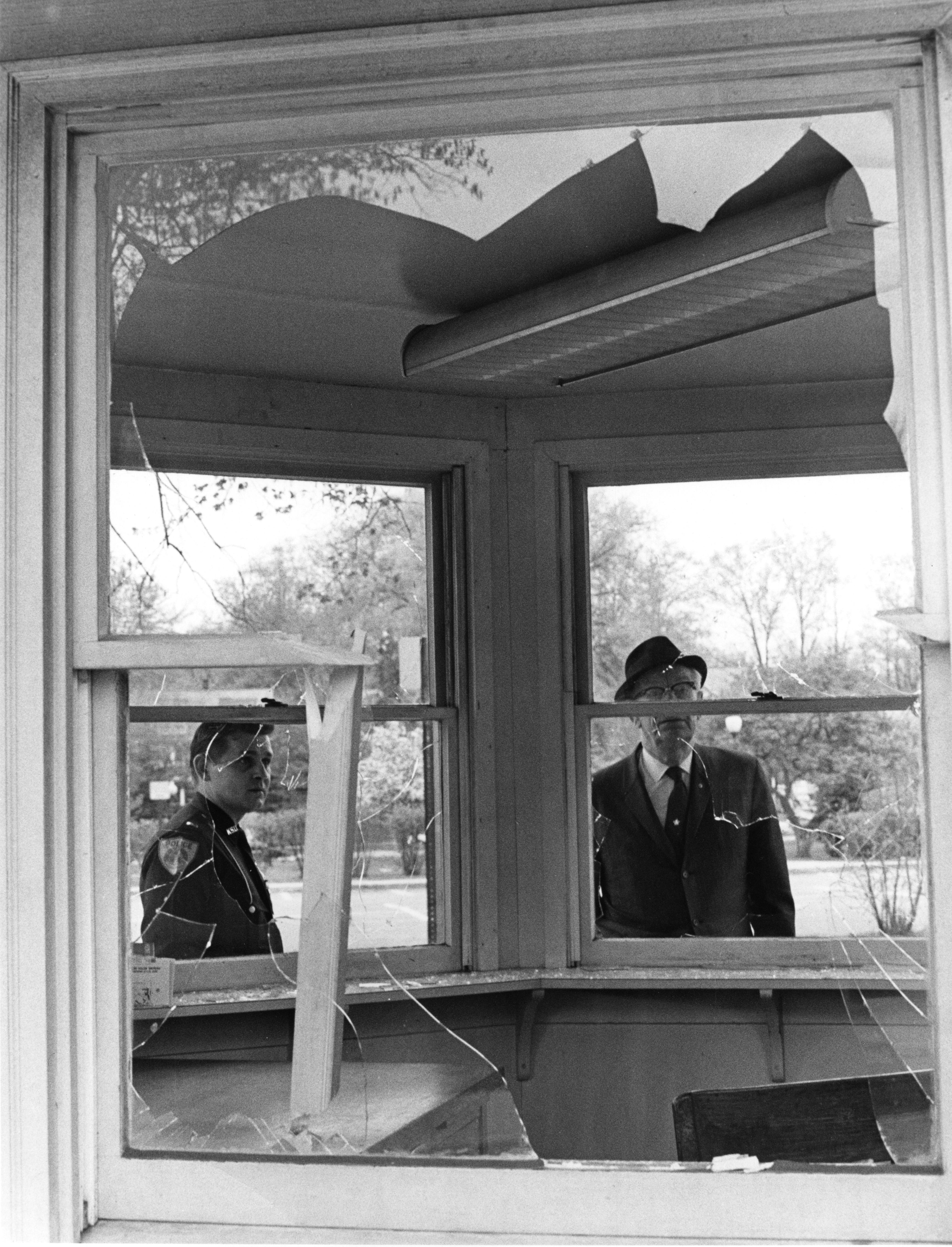 A Kent State policeman and Emil Berg, Kent State's business manager, survey the smashed windows in the visitor information kiosk on campus near Rockwell Hall following a night of vandalism on May 1, 1970. Protesting students left many Kent businesses with broken windows and damaged buildings.