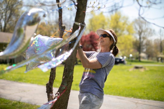 Barb McGrath, of Blue Ash, hangs balloons and streamers in a front yard in Tangleridge subdivision, Wednesday, April 22, 2020. A few weeks ago, McGrath started doing some chalk work and adding streamers to a neighbor's house. They, in turn, hung streamers in her yard.