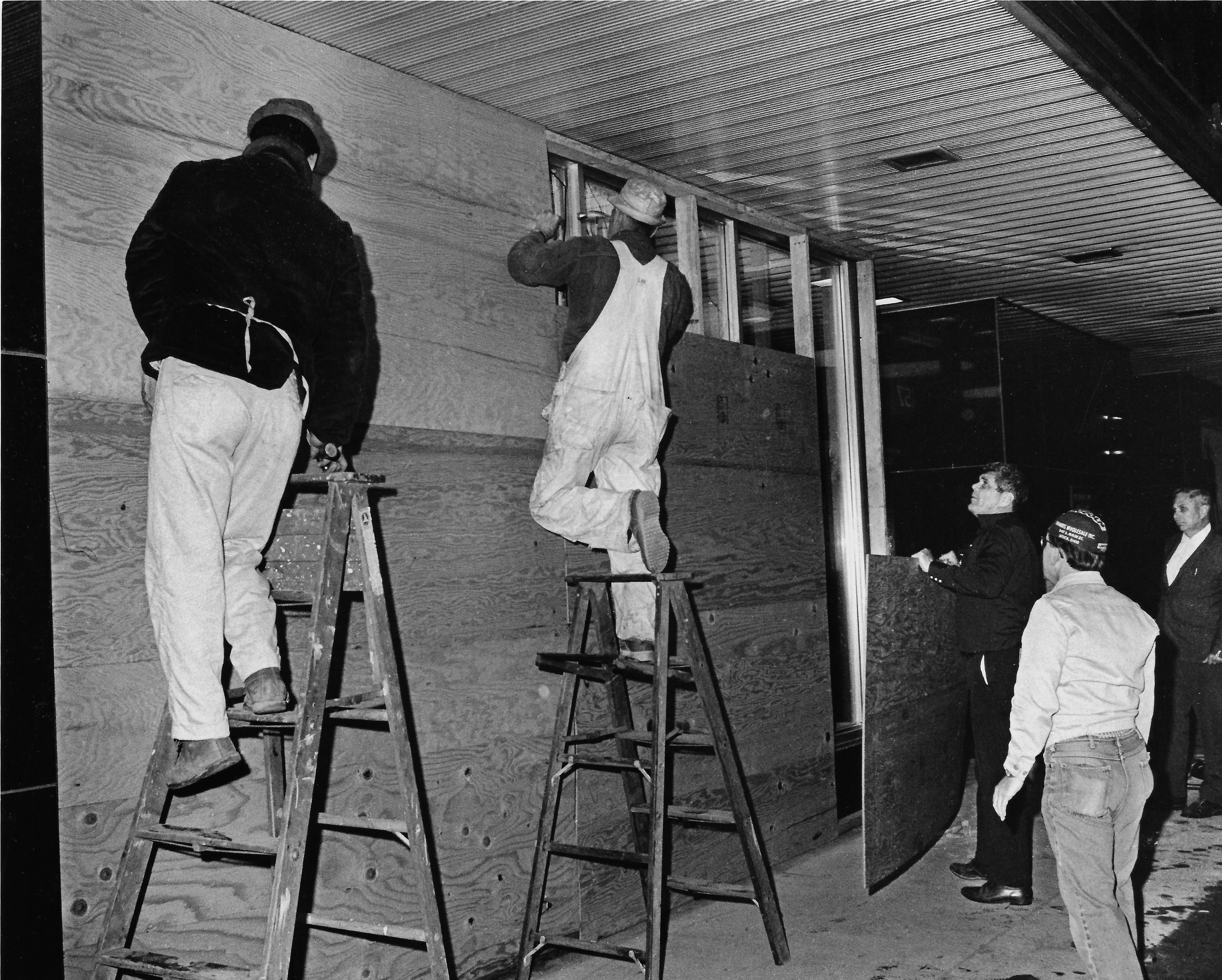 Workers board up broken windows on the First Federal Savings Bank building after vandals damaged a number of buildings in downtown Kent Friday night, May 1, 1970.