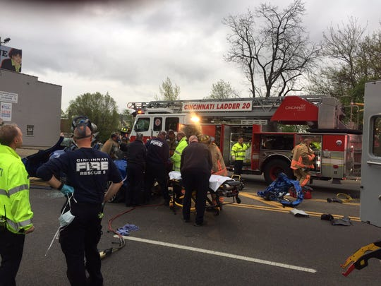 Cincinnati firefighters prepare to load a patient from a Thursday morning car crash in the 5400-block of Colerain Avenue into an ambulance.