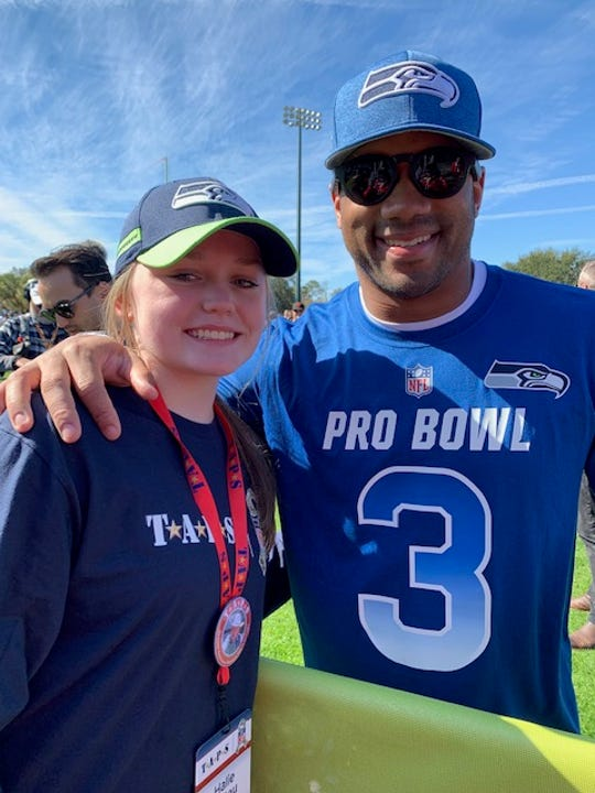 Halie Ristau poses for a photo with Seattle Seahawks quarterback Russell Wilson. Ristau got to meet the NFL player through a program that helps families cope with the grief of losing a loved one in the armed services. Halie's brother, Michael, was killed in Afghanistan.