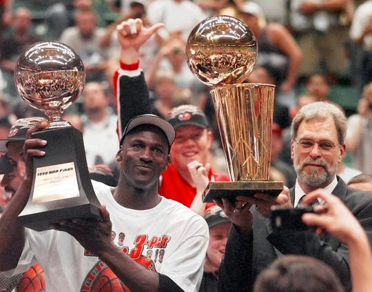 Bulls' Michael Jordan holds the NBA Finals MVP trophy as coach Phil Jackson holds the Larry O'Brien NBA championship trophy after the Bulls defeated the Utah Jazz, 87-86, in Game 6 in Salt Lake City, Sunday, June 14, 1998.