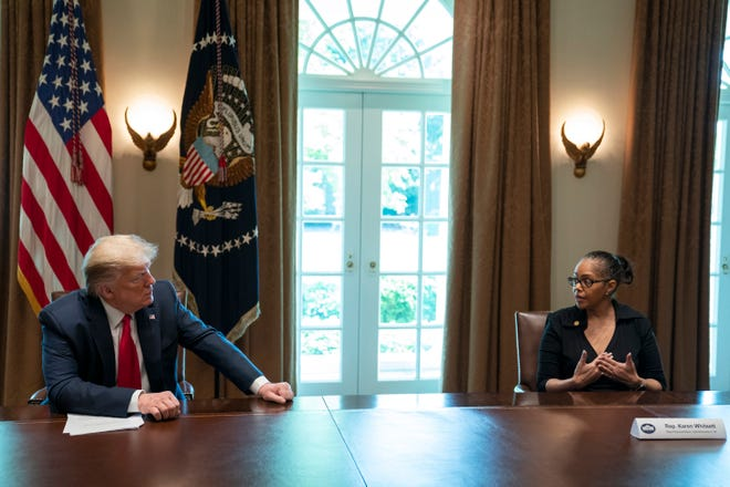 President Donald Trump listens as Karen Whitsett shares her story of recovery from COVID-19, in the Cabinet Room of the White House, Tuesday, April 14, 2020, in Washington.