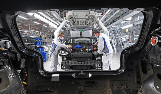 Max Bruehmann (l) and Heiko Gruner employees of German car producer Volkswagen Sachsen, work with face masks in the assembly of the ID.3 in the vehicle plant in Zwickau, Germany, Thursday, April 23, 2020.