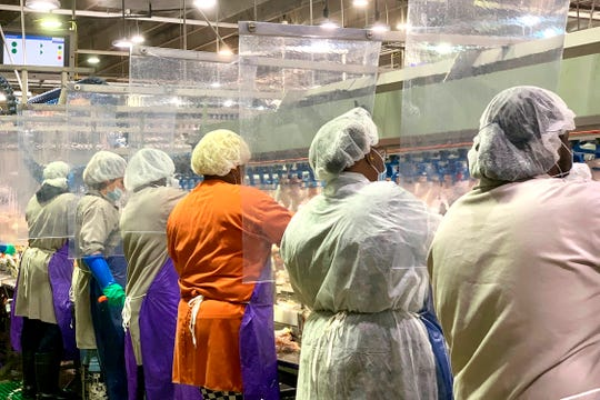 In this April 2020, photo provided by Tyson Foods, workers wear protective masks and stand between plastic dividers at the company's Camilla, Georgia poultry processing plant.