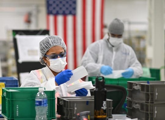 Michelle Heath, quality inspector, Project M, General Motors, examines each face mask made at the Warren transmission plant on Thursday, April 23, 2020.