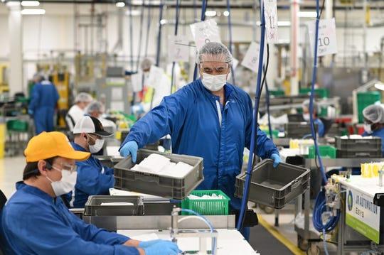 Nick Sinishyaj, center, gathers finished face masks made at the Warren transmission plant on Thursday, April 23, 2020.