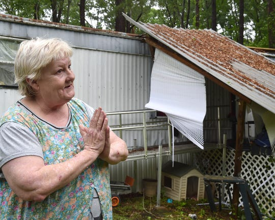 Former nurse and Marine Denise Thornton stands adjacent to a damaged mobile home that sustained damage on her property during a severe storm that struck the unincorporated area of Rankin County in the early hours Thursday in Monterey, Miss.