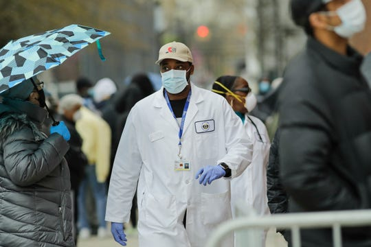 A medical worker walks past people lined up at Gotham Health East New York, a COVID-19 testing center Thursday, April 23, 2020, in the Brooklyn borough of New York.