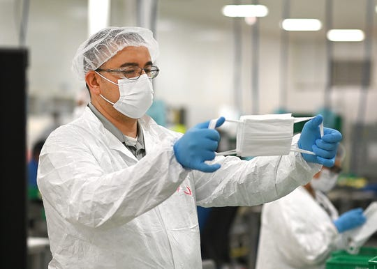 Chasan Karadsheh, quality inspector, Project M, General Motors, stretches and examines the finished face masks made at the Warren transmission plant on Thursday, April 23, 2020.