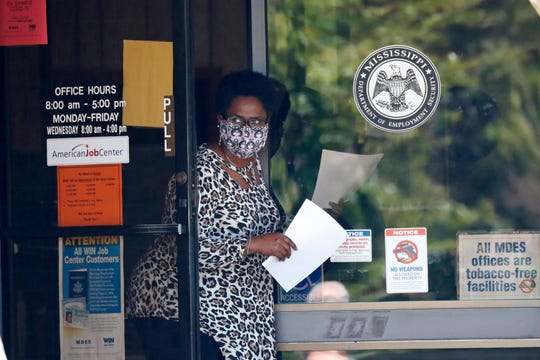 A masked worker at this state WIN job center in Pearl, Miss., holds an unemployment benefit application form as she waits for a client, Tuesday.