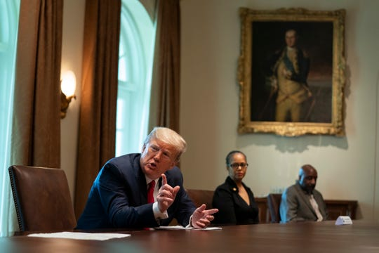 Karen Whitsett, center, and her husband Jason Whitsett, right, listen as President Donald Trump speaks during a meeting with people that have recovered from COVID-19, in the Cabinet Room of the White House, Tuesday, April 14, 2020, in Washington.