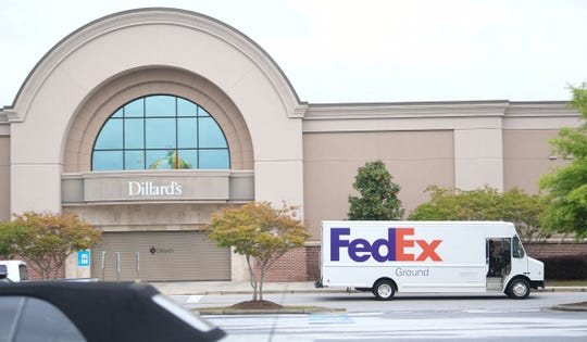 A FedEx truck making deliveries drives away from a closed Dillard's anchor store at the Anderson Mall in Anderson, S.C. Thursday, April 23, 2020. The mall plans to open Friday, April 24, 2020, with reduced hours of 11 a.m. to 7 p.m. Monday through Saturday, and noon to 6 p.m. Sunday.  Gov. Henry McMaster issued an executive order reopening retail stores that were closed due to coronavirus, with strict social distancing requirements of 20 percent capacity and following relevant CDC and DHEC guidelines.