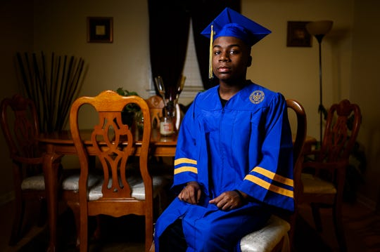 Travelers Rest High School senior Cameron Lomax-Byrd poses for a portrait dressed in his graduation cap and gown inside his home Thursday, April 23, 2020.