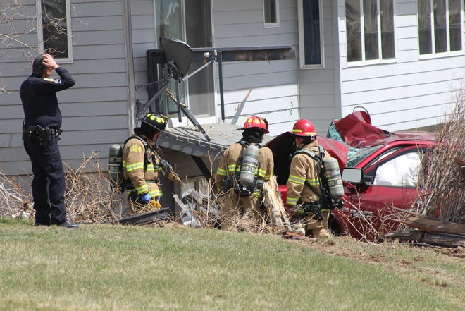 A Great Falls police officer scratches his head as first responders from Great Falls Fire Rescue respond to the crash at 229 Skyline Drive NE.