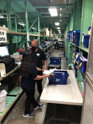Workers at NEX Guam process orders placed by USS Theodore Roosevelt sailors.