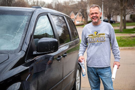 Iowa City Regina art teacher John Demory poses for a photo while delivering supplies to students, Wednesday, April 22, 2020, in Iowa City, Iowa.