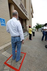 Hinds County residents stand in marked boxes, 6 feet from each other along a line leading to the entrance of the county's Chancery Court building where the tax assessor and tax collector's offices are located in Jackson, Miss., Wednesday, April 22, 2020.