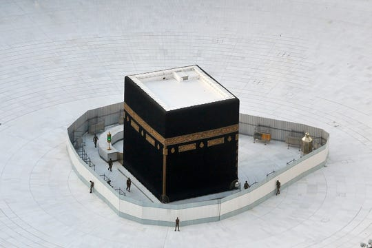 Police guard the the Kaaba, the cube building at the Grand Mosque, in the Muslim holy city of Mecca, Saudi Arabia, Friday, March 6, 2020. Saudi Arabia emptied Islam's holiest site for what they say sterilization over fears of coronavirus.