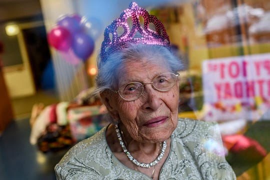 Eva Salinas wears a tiara while visiting with friend Traci Ruiz though a window on Eva's 101st birthday on Thursday, April 23, 2020, at the Ingham County Medical Care Facility in Okemos. Ruiz organized the birthday celebration for Salinas to enjoy from a window due to coronavirus restrictions.