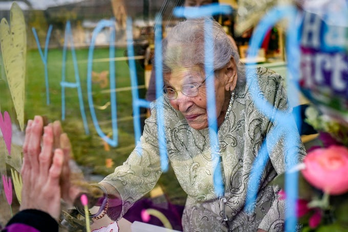 Eva Salinas holds her hand up to the hand of friend Traci Ruiz through a window on Eva's 101st birthday on Thursday, April 23, 2020, at the Ingham County Medical Care Facility in Okemos. Ruiz organized the birthday celebration for Salinas to enjoy from a window due to coronavirus restrictions.