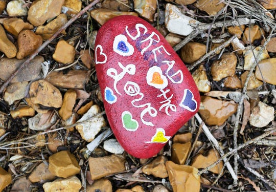 A painted rock near a bush shows the love and joy of hearts during the coronavirus crisis, Thursday, April 23, 2020, in Two Rivers, Wis.