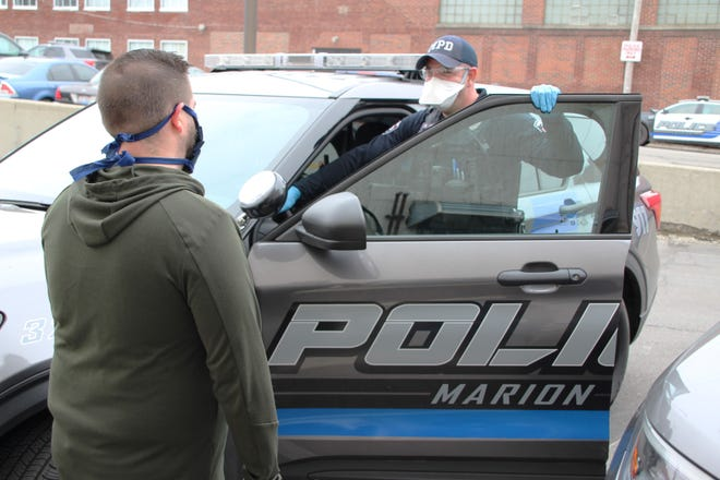 Officer Matt Creps, right, of the Marion Police Department talks with fellow department employee Dustin Evans prior to heading out on patrol Thursday morning. Creps is shown wearing some of the additional personal protective equipment Chief Bill Collins has ordered all officers to wear while on duty to protect themselves during the coronavirus pandemic.