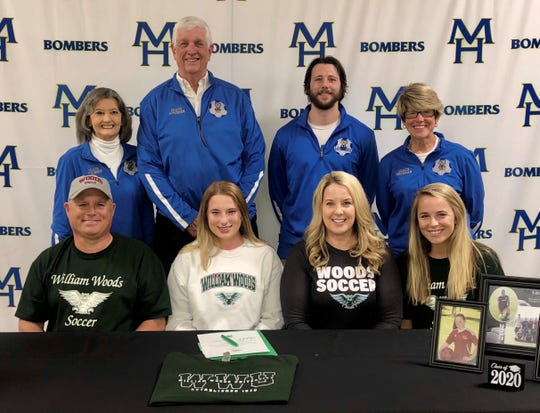 Mountain Home's Lauren Helmert (front row, second from left) signed Thursday to play college soccer at William Woods University in Fulton, Mo. Pictured with Helmert are: (front row) father Eddie Helmert, mother Stacy Helmert, sister Ana Helmert; (back row) Lady Bomber head coach Debbie Atkinson, MHHS assistant coach Max Atkinson, MHHS assistant Ian Biggs, and MHHS assistant Cathy Beckham.