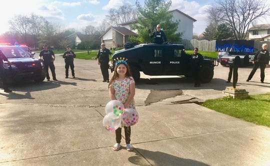 Officers from the Muncie Police Department pose for a picture with one of the area residents they provided a birthday parade for.