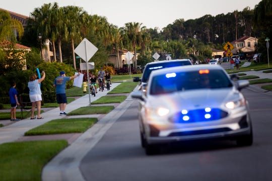 Collier County Sheriff's Office deputies drive down the street while community members cheer and hold up signs during a neighborhood demonstration of appreciation for healthcare workers and first responders at Marbella Isles in Naples on Wednesday, April 22, 2020.