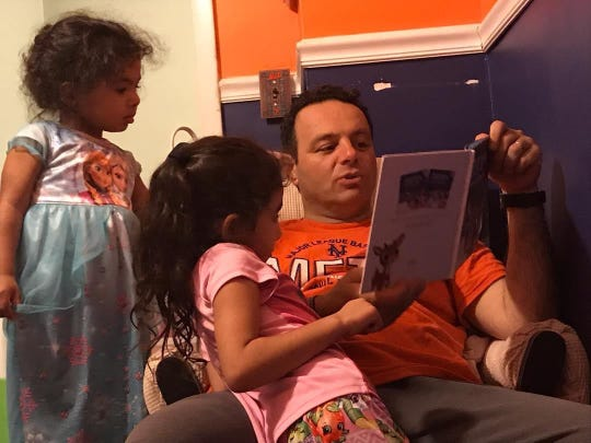 Mayor Andre Sayegh of Paterson reading to his children Kayla, 4, and Sophia, 6 (Photo courtesy: Andre Sayegh)