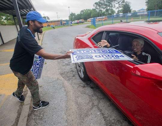 Josh Steen passes out a sign to a senior at Washington High School on Thursday, April 23, 2020. Educators and staff at Washington gathered at the school on Thursday to hand out yard signs and t-shirts to this year's 12th-graders as a way to foster class unity.