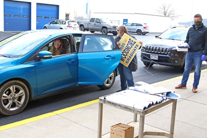 Woodmore senior Julia Cuevas drives up to the high school to pick up her graduation cap and gown on Thursday morning. Senior adviser Whitney Flick gave out yard signs and banners while Jason Miller from Josten Graduation Services passed out caps and gowns.