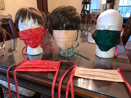 Hilary Richards, a quilter from Poughkeepsie, tries her homemade surgical masks on mannequin faces before sending batches each week to the oncology staff at White Plains Hospital.