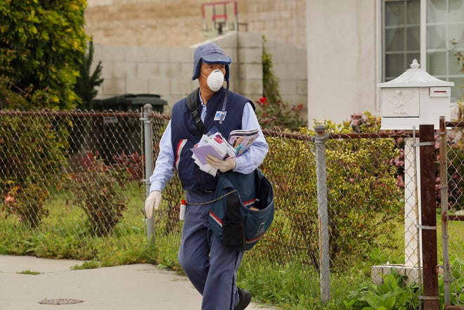 A postal worker delivers mail in Torrance, wearing a mask and gloves on March 14, 2020. Experts warn against a false sense of security. (Carolyn Cole/Los Angeles Times/TNS)