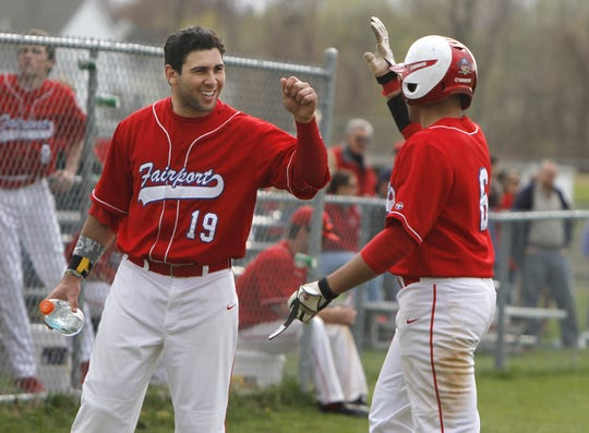 Fairport's Connor Simonetti, left, celebrates with teammate Tyler Dardzinski, right, after both scored against Irondequoit in the first inning during their Section V baseball matchup played at Fairport High School on April 25, 2013.