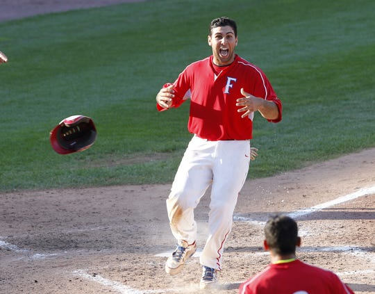 Fairport's Connor Simonetti crosses home plate for the walk-off winning run during Class AAA championship baseball action between the Rush-Henrietta Royal Comets and the Fairport Red Raiders at Frontier Field in Rochester on May 30, 2013. Fairport won the title with a 4-3 victory over R-H.
