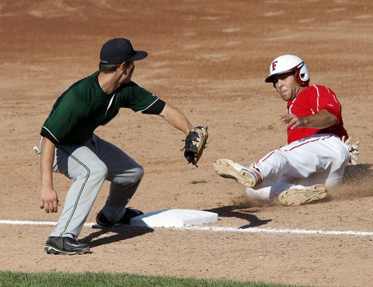 Fairport's Connor Simonetti, right, slides in safely for a triple against R-H's Tommy Kirch during Class AAA championship baseball action between the Rush-Henrietta Royal Comets and the Fairport Red Raiders at Frontier Field in Rochester on May 30, 2013.
