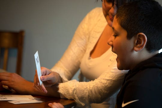 """Suleika McCaughey practices letters with her son Sami Adham, 8, as the """"school day"""" starts around 9 a.m. at their home in Salem on April 23, 2020."""